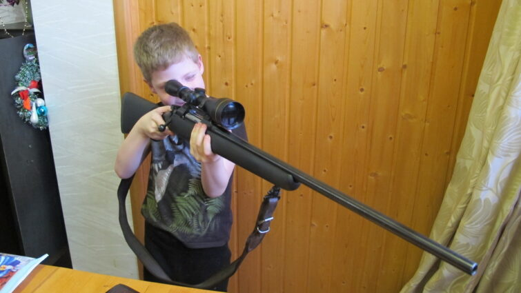 Сын держит винтовку в руках
